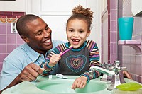 African father helping daughter brush her teeth