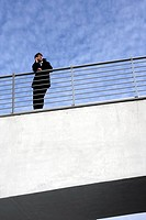 A businessman leaning on a railing with a mobile phone