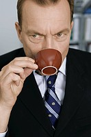 Businessman drinking out of coffee cup