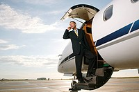 Businessman standing on a private airplane's steps