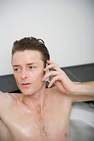 Man sitting in a bathtub and using a mobile phone