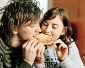 Teenage couple sharing slice of pizza
