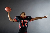 Mixed race quarterback throwing football