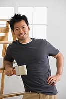 Asian man holding paintbrush