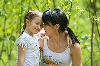 Mother and daughter embracing in a forest