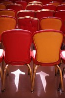 Red and beige chairs under spotlight in auditorium
