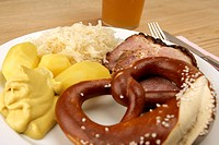 Plate with pork, sauerkraut, potato, and pretzel next to glass of beer