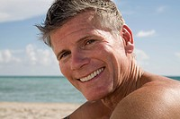 Man sitting on the beach and smiling
