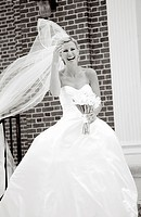 Bride standing on steps with veil blowing in the wind