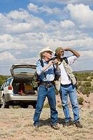 Men on remote roadside looking into distance