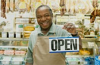 African butcher holding Open sign