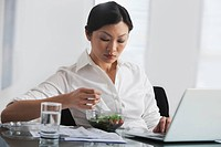 Chinese businesswoman eating salad at desk