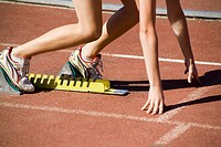 Female athlete running from starting blocks