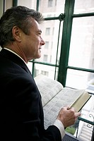 Businessman standing by a window holding a book