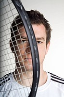Portrait of a tennis player holding a tennis racquet infront of his face