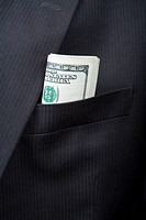 Detail of folded US bank notes in a suit pocket