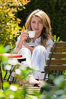 Young woman drinking a cup of coffee for breakfast in the garden