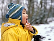 A young boy licking a snowball