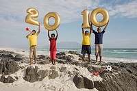 Boys standing on rocky outcrop, holding golden balloons shaped as numbers for 2010, Table Mountain in background, Blouberg Beach, Cape Town, Western C...
