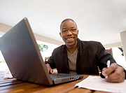 Young businessman looks up from laptop while working at home, Johannesburg, Gauteng Province, South Africa