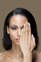 Portrait of a woman with her hand in front of her face