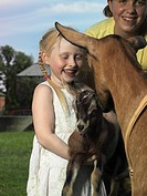 Two girls with a a goat and it´s kid