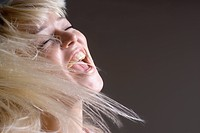 A woman tossing her hair with her mouth open