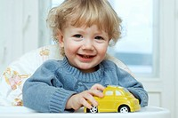 A young boy sitting in a high chair playing with a toy car
