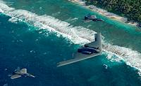 Two F-22 Raptors and a B-2 Spirit bomber deployed to Andersen Air Force Base, Guam, fly in formation over the Pacific Ocean  The deployment to Anderse...