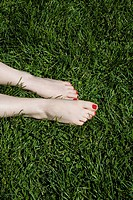 A young woman´s bare feet with red painted toenails lying on grass