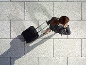 A businesswoman pulling a suitcase and talking on her mobile phone