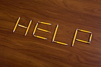 Pencils on a table arranged to spell Help