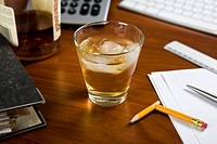 A glass of whiskey and ice on an office desk