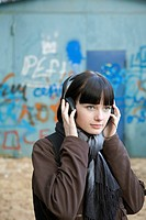 A teenage girl wearing headphones, outdoors