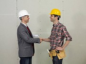 An architect shaking hands with a construction worker