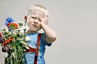 A young boy with a bunch of flowers pouting