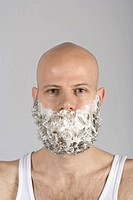 A man with shaving cream all over his beard