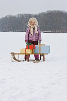A young girl with a sled with presents