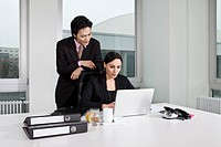 A businessman and a businesswoman looking at a laptop
