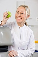 Portrait of a dental assistant holding an apple