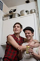A young couple standing together in a kitchen