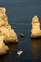 Boats pass through seastacks at Ponta De Piedade near Lagos in the Algarve, Portugal