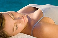 Young woman lying on massage table by the pool