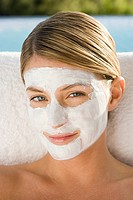 Young woman with facial mask on sitting by pool