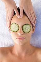Young woman with cucumber slices over eyes receiving facial massage