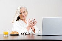 Middle aged woman eating breakfast while using laptop