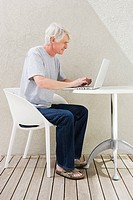 Middle aged man sitting on desk and using laptop