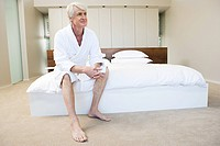 Middle aged man in bathroom sitting on edge of bed (thumbnail)