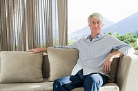 Portrait of middle aged man sitting on couch