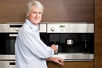 Middle aged man waiting for coffee from coffee machine